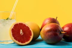 Close-up view of fresh ripe grapefruits and mangoes and glass with cold summer drink on yellow stock photo