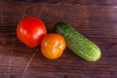 Close up view of fresh, ripe tomatoes and cucumbers on wood back Royalty Free Stock Photos