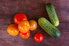 Close up view of fresh, ripe tomatoes and cucumbers on wood back Stock Image