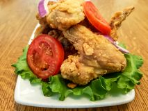 Fried chicken wings and tomatoes with lettuce on a white plate - fast food restaurant meal. Close-up view of fried chicken wings and tomatoes with lettuce on a royalty free stock image