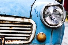 Close-up view on the front-left part of an old broken car. A close-up view on the front-left part of an old rusty and broken blue car - photo royalty free stock image