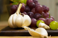 Close up view of garlic and red and yellow muscat colored grapes Royalty Free Stock Images
