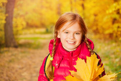 Close-up view of girl with rucksack and maple leaf. Close-up view of girl with rucksack standing alone with maple leaf in the forest during autumn daytime Royalty Free Stock Images