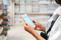 Close up view girl using smartphone in store. Close up view girl buy products using smartphone in store. Young woman shopping in supermarket blur background royalty free stock photos