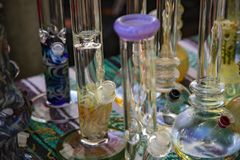 Handcrafted Glass Bongs on Flea Market Table. Close Up View Glass Bongs on Flea Market Table, Sunlit Out of Focus Background, Backdrop, Copy Space Use Overlay stock image