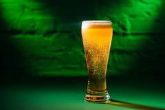 Close-up view of glass with fresh cold amber beer in green light, saint patricks. Day concept stock photography