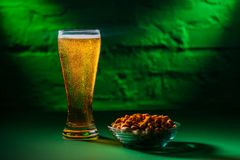 Close-up view of glass with fresh cold beer and salted peanuts. On plate stock images