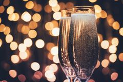 Glasses of champagne with bubbles. Close up view of glasses of champagne with bubbles against festive lights Stock Photography
