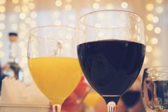 Close-up view of glasses with red wine and orange juice on a table in restaurant at the garlands curtain background. Filled glasse. S on a served restaurant royalty free stock image