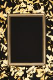 Close up view of golden confetti and photo frame. Isolated n black Royalty Free Stock Photos