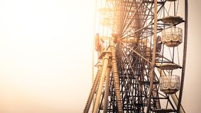 Ferris wheel lit by the warm glow of the sun stock photo