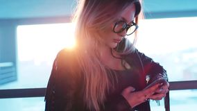 Close up view of gorgeous blonde woman in casual wear using her phone in a bright sunshine. City on the background stock video