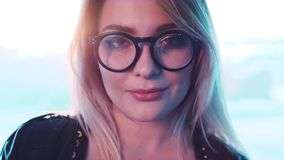 Close up view of a gorgeous young blonde woman in eyeglasses looking to camera and playfully smiling. Natural beauty stock video footage