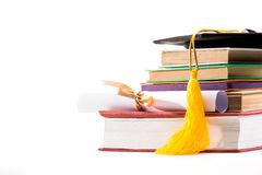 Close-up view of graduation mortarboard, books and diploma on white background royalty free stock photography