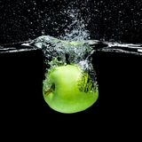 Close up view of green apple falling into water. Isolated on black royalty free stock photo