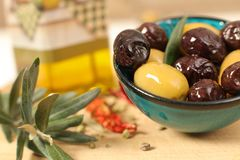 Close up view of green and black olives in porcelain bowl with o. Live oil  with fresh bread, young olive branch , thyme and pepper on wooden background Stock Photo