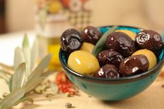 Close up view of green and black olives in porcelain bowl with o. Live oil  with fresh bread, young olive branch , thyme and pepper on wooden background Royalty Free Stock Photography