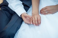 Close-up view of the groom holding the hand of his bride with the wedding ring. royalty free stock photo