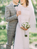 The close-up view of the groom hugging the bride with the wedding bouquet back. Stock Photo