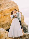 The close-up view of the groom kissing the bride with the wedding bouquet while standing on the cliff. The close-up view of the groom kissing the bride with the Royalty Free Stock Photography