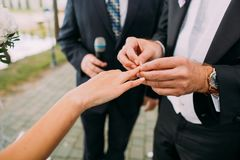 Close-up view of the groom putting the wedding ring on the finger of the bride. stock images