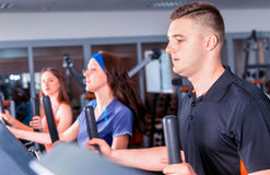 Close up view on group of people diligently exercising on the cr. Osstrainer machines in fitness center Stock Photo