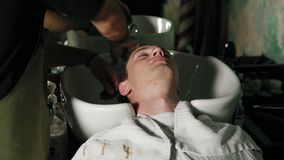 Close up view of hairdresser hands washing male head at barbershop. Hairdresser washing attractive man`s hair.  stock video