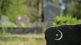 Close up view of half moon, crescent moon symbol on a granite grave monument in a cemetery on a sunny day