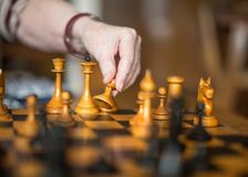 Close-up view of a hand of elderly woman playing chess.  stock images