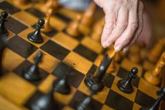 Close-up view of a hand of elderly woman playing chess.  stock photography