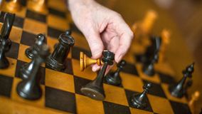 Close-up view of a hand of elderly woman playing chess.  stock image
