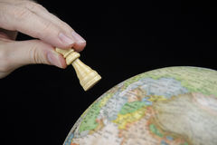 Close-up view of a hand holding a chess piece over a globe isolated Royalty Free Stock Image
