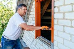 Closeup view on hand holding paintbrush. Senior man painting wooden windows using paintbrush. Repairing exterior of old house royalty free stock image