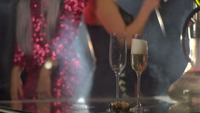Close-up view of the hand pouring the champagne into glasses at the blurred background of the dancing girlfriends. stock video