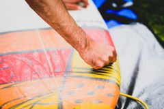 Close up view of hand waxing surf board outdoors. Man is removing or applying wax to surfboard shortboard on vacation. Traces of wax are visable Stock Images