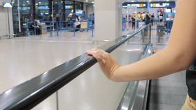 Close-up view of hand of woman using an airport walkway stock footage