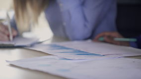 Close-up view on hands of employees, analyzing statistics indoors. stock video footage