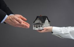 Close up view of hands giving house model to other hands Stock Images