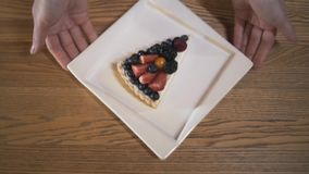 Close-up view of hands holding a white plate with delicious cheesecake covered by blueberries, blackberries and. Strawberries and putting it on the table. Tasty stock video footage