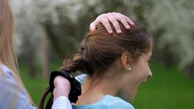 View hands of little girl playing with tying up girlfriend hair in a plait or braid, lifestyle friendly relations. Close up view hands of little girl playing stock video footage