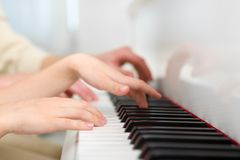 Close up view of hands playing piano Stock Photo