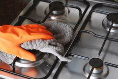 Close up view of hands in rubber gloves cleaning hob Stock Photography