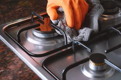 Close up view of hands in rubber gloves cleaning hob royalty free stock images