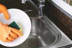 Hands in rubber gloves washing dishes with spon royalty free stock image
