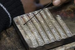 Silver jewel worker, Inle Lake. Close up view of the hands of a silver jewelry worker and other precious minerals. Use of traditional work tools stock image