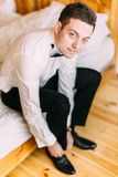 Close-up view of the handsome groom tying the wedding shoes. Close-up view of the handsome groom tying the wedding shoes Stock Image