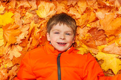Close up view of happy boy laying on autumn leaves Royalty Free Stock Photos