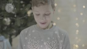Close up view on happy excited boy kid opening christmas present gift box surprised in awe sitting near new year tree. Close up view on happy excited kid boy stock video footage