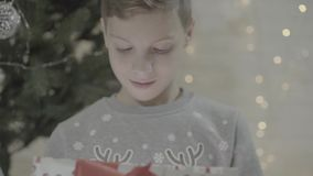 Close up view on excited happy kid boy opening christmas present gift box surprised in awe sitting near new year tree. Close up view on happy excited kid boy stock video footage