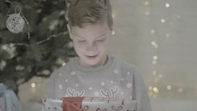 Close up view on happy excited kid boy opening christmas present gift box surprised in awe sitting near new year tree stock video
